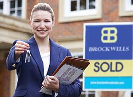 Female Realtor Standing Outside Residential Property Holding Key