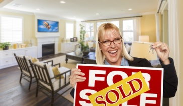 Happy Young Woman Holding Sold For Sale Real Estate Sign and Keys Inside Beautiful Custom Living Room.