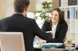 Businesspeople handshaking after negotiation or interview at office