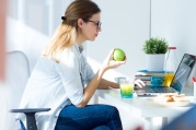 Portrait of pretty young woman eating an apple and working at home.