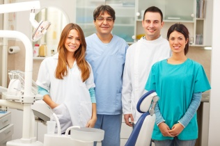 Group of dentists standing in their office and looking at camera.