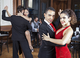 Confident Man And Woman Performing Tango In Restaurant