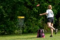 Women outside playing disc golf by throwing a disc towards a target