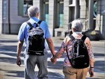 Older couple with back packs holding hands walking away from camera