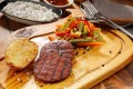 Wooden cutting board with cooking vegetables, steak, and roll